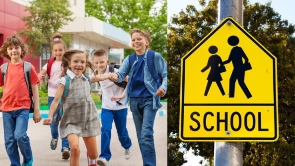 Children walking with backpacks and school zone sign